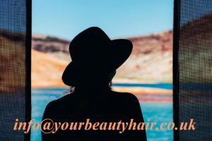 Silhouette of a woman in hat, sea in the background
