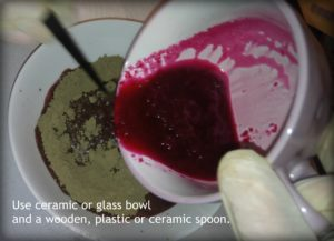 Adding beetroot mixture to henna powder.