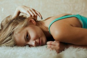 Blond woman lying on a furry blanket.
