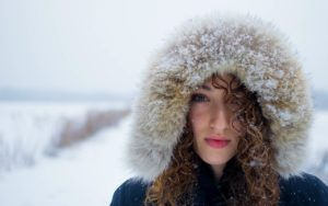 A woman with curly hair, wearing furry hood.