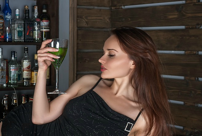 A woman with a glass of alcohol.